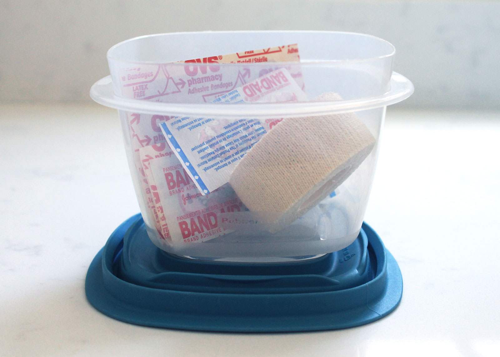 Repurpose plastic containers to store first aid kits